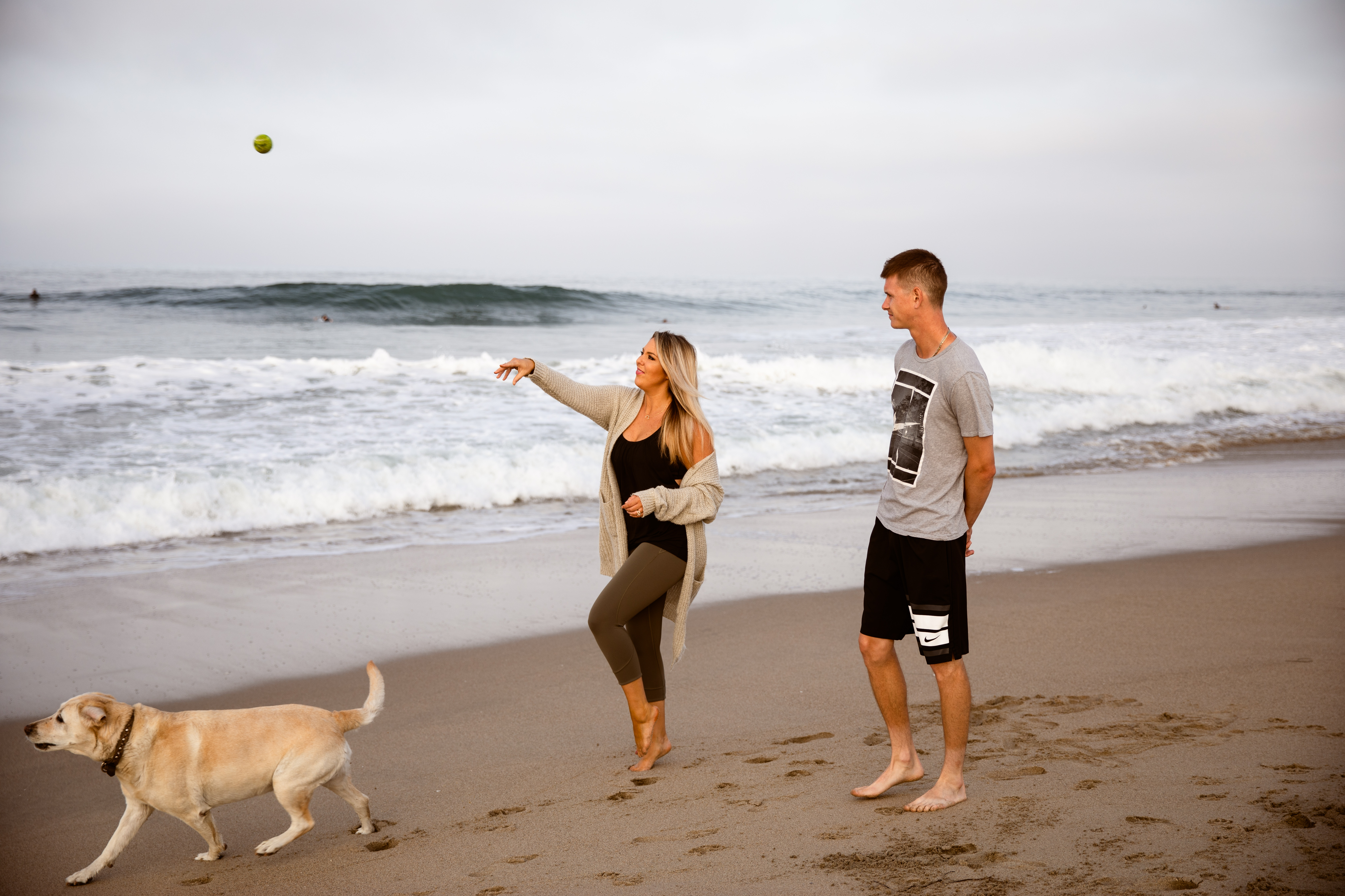 Newport Beach couple walking playing fetch with dog